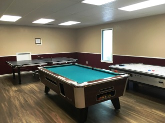 Game room with pool table, ping pong table, and air hockey.